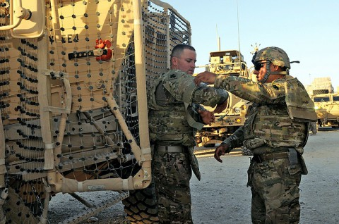 U.S. Army Sgt. Osbaldo Espinoza, right, a platoon team leader, and Spc. Dustin J. Johnson, motor transport operator, both with the 3rd Platoon, 1245th Transportation Company, 1034th Combat Sustainment Support Battalion, assist each other with straps on their improved outer tactical vest as they prepare for their convoy escort team mission at Mazar-e-Sharif, Balkh province, Afghanistan, June 18, 2013. (U.S. Army photo by Sgt. Sinthia Rosario/Released)