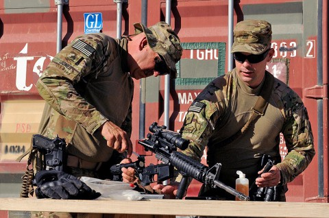 U.S. Army Sgt. Robert P. Jones, left, and Sgt. Brian C. Thomas, both motor transport operators with the 3rd platoon, 1245th Transportation Company, 1034th Combat Sustainment Support Battalion, clean weapons in preparation for their convoy escort team mission, at Mazar-e-Sharif, Balkh province, Afghanistan, June 18, 2013. (U.S. photo by Sgt. Sinthia Rosario/Released)