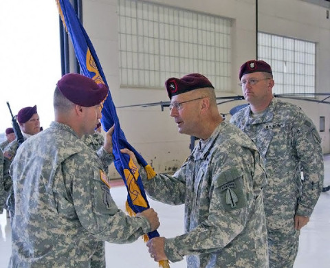 Maj. Jeffery J. Bragg, who has served in the 160th SOAR (A) since 2010, most recently as the Regiment S3, receives the SOATB guidon from Brig. Gen. Clayton M. Hutmacher as he takes command Friday.   Looking on is outgoing commander Lt. Col. Mark. G. Kappelmann, whose next assignment is to command the 1-214th Aviation Regiment in Germany. (U.S. Army photo)