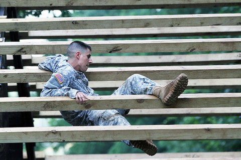 """Sgt. Ryan Thayer, an Avenger crew member for Battery A, 2nd Battalion, 44th Air Defense Artillery Regiment, 101st Sustainment Brigade, 101st Airborne Division (Air Assault), weaves his body through the boards of the Weaver June 19, at the Sabalauski Air Assault School at Fort Campbell. Thayer is taking part in """"Strike Fear Week"""". (U.S. Army photo by Sgt. Leejay Lockhart, 101st Sustainment Brigade Public Affairs)"""
