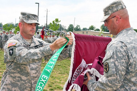 The Fort Campbell Warrior Transition Battalion command team, Col. William Howard and Command Sgt. Maj. James Smith, pin the Department of the Army Safety Excellence Streamer to the WTB colors during a ceremony June 5th. (U.S. Army photo by Stacy Rzepka/Released)