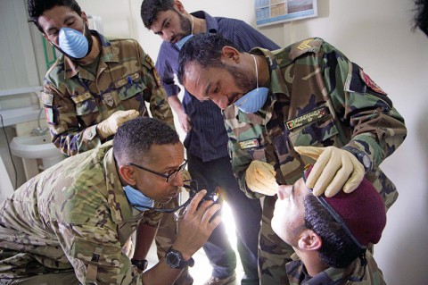 U.S. Capt. Abby Raymond, a brigade dentist with the 4th Brigade Combat Team, 101st Airborne Division (Air Assault), checks the work of an Afghan medic with the 2nd Commando Battalion, 203rd Corps, Afghan National Army, performing an oral exam on a fellow commando during a basic dental class at Forward Operating Base Thunder in Paktia province, Afghanistan, July 22, 2013. (U.S. Army photo by Sgt. Justin A. Moeller/Released)