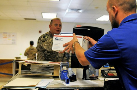 A postal clerk accepts a Priority Mail box from Lt. Col. Derek G. Bean, commander of the 101st Special Troops Battalion, Task Force Lifeliner, for inspection during the kick-off of the Click-N-Ship program that was implemented at the post office at Bagram Air Field in Parwan province, Afghanistan, July 14th, 2013. (Sgt. Sinthia Rosario)