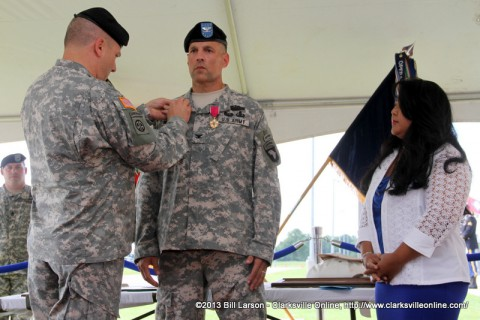 Brig. Gen. Mark R. Stammer pins the Distinguished Member of the Regiment pin on Col. Daniel R. Walrath as Col. Walrath's wife Christine looks on.