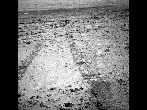 "This view from the left Navigation Camera (Navcam) of NASA's Mars Rover Curiosity looks back at wheel tracks made during the first drive away from the last science target in the ""Glenelg"" area. The drive commenced a long trek toward the mission's long-term destination: Mount Sharp. (NASA/JPL-Caltech)"