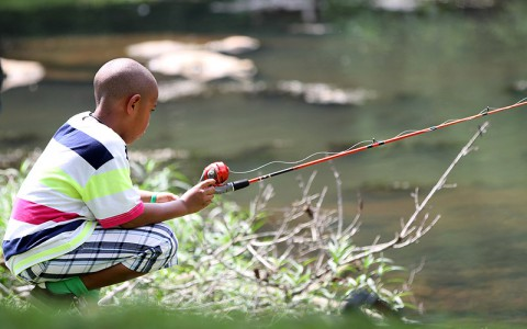 Camper Apollo Kim, 8, enjoys a peaceful moment fishing July 10th, at Fort Campbell, KY. The goal of the Fort Campbell Survivors Outreach Services Camp SOS is for the children to have a week of fun. (U.S. Army photo by Sgt. Leejay Lockhart, 101st Sustainment Brigade Public Affairs)
