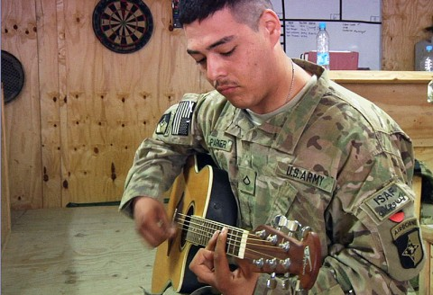 U.S. Army Pfc. Joseph Parker, a unit supply specialist with the 58th Signal Company, plays his guitar prior to reporting to work August 1st, 2013 in Hairatan, Balkh province, Afghanistan. (U.S. Army photo by Staff Sgt. Peter Sinclair/Released)