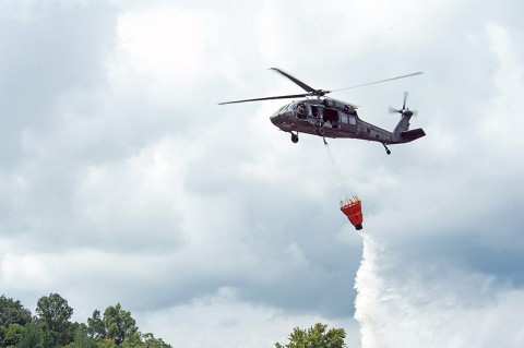 A UH-60 Black Hawk helicopter with A Company, 6th Battalion, 101st Combat Aviation Brigade, 101st Airborne Division (Air Assault), dumps water out of a bucket slung from the helicopter during wildfire operations training at Fort Campbell, Ky., Aug. 19, 2013. (U.S. Army photo by Sgt. Duncan Brennan, 101st CAB Public Affairs)
