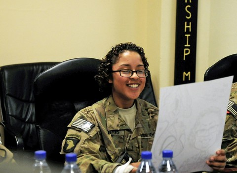 U.S. Army Pvt. Alice M. Harris, a human resource specialist with the Headquarters and Headquarters Battalion, 101st Airborne Division (Air Assault), looks a her caricature drawn by MAD Magazine cartoonist Tom Richmond at Kandahar Airfield, in Parwan Province, Afghanistan, Sept. 6, 2013. Eight nationally recognized members of the National Cartoonists Society were part of a USO tour in Afghanistan. (U.S. Army photo by Sgt. Sinthia Rosario/Released)