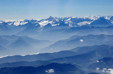This photo from summer 2012 looking south into the Bernese Alps shows how air pollution in the Alps tends to be confined to lower altitudes, concentrating the deposition of soot and dust on the lower slopes. At center left in the picture, a glacier can be seen extending from a high-altitude snow field, above the pollution layer, down into the valley where its lower reach is bathed in pollutants. (Image credit: Peter Holy)