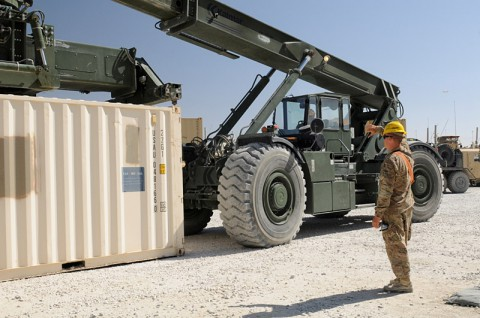U.S. Army Spc. Casey E. Sleeman, a native of Sioux Falls, SD, and a cargo specialist, ground-guides and conducts arm and hand signals for U.S. Army Spc. Kevin E. Berry, a native of Grantsburg, WI, and a materials handler equipment operator, as Berry prepares to pick up a container with a Kalmar RT-240 Rough Terrain Container Handler. (U.S. Army photo by Sgt. Sinthia Rosario, Task Force Lifeliner Public Affairs)