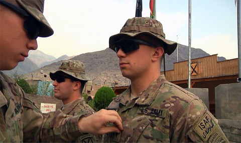 Second Lt. Karl F. Knowlton, air mobility deputy with Task Force Lifeliner, prepares to strip the specialist rank off the uniform of newly promoted Sgt. George C. Knowlton, a team leader with 3rd Squadron, 89th Cavalry, 4th Infantry Brigade Combat Team, 10th Mountain Division, during a promotion ceremony, at Forward Operating Base Wright, Kunar province, Afghanistan. Both brothers are from Winder, GA. (U.S. Army photo by Staff Sgt. Peter R. Sinclair, Task Force Lifeliner Public Affairs)