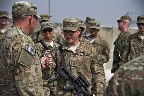 U.S. Army Pfc. John L. Wempe, a human resources specialist with 1st Squadron, 61st Cavalry Regiment, 4th Brigade Combat Team, 101st Airborne Division (Air Assault), is handed a pair of gold spurs, during a spur ceremony at Camp Clark, Afghanistan, Oct. 11, 2013. (U.S. Army photo by Sgt. Justin A. Moeller, 4th Brigade Combat Team Public Affairs)