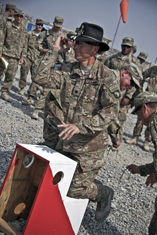 U.S. Army Lt. Col. Thomas T. Sutton, commander of 1st Squadron, 61st Cavalry Regiment, 4th Brigade Combat Team, 101st Airborne Division (Air Assault), kneels on a platform as gold spurs are put on his boots, during a spur ceremony at Camp Clark, Afghanistan, Oct. 11, 2013. (U.S. Army photo by Sgt. Justin A. Moeller, 4th Brigade Combat Team Public Affairs)