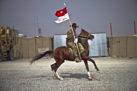 U.S. Army 1st Lt. Jeremy A. Woodard, an engineer officer with 1st Squadron, 61st Cavalry Regiment, 4th Brigade Combat Team, 101st Airborne Division (Air Assault), rides a horse while holding the Headquarters Troop Guidon, during a spur ceremony at Camp Clark, Afghanistan, Oct. 11, 2013. (U.S. Army photo by Sgt. Justin A. Moeller, 4th Brigade Combat Team Public Affairs)
