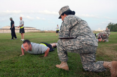 Staff Sgt. Marleny Castrejon, Headquarters and Headquarters Company, 101st Combat Aviation Brigade, 101st Airborne Division (Air Assault,) taskings noncommissioned officer grades Staff Sgt. Ronnie Ables, D Company, 1st Battalion, 101st CAB, technical inspector on his pushups during an Army physical fitness test held at 101st CAB headquarters, Fort Campbell, Ky., Oct. 9, 2013. (U.S. Army photo by Sgt. Duncan Brennan, 101st CAB Public Affairs)