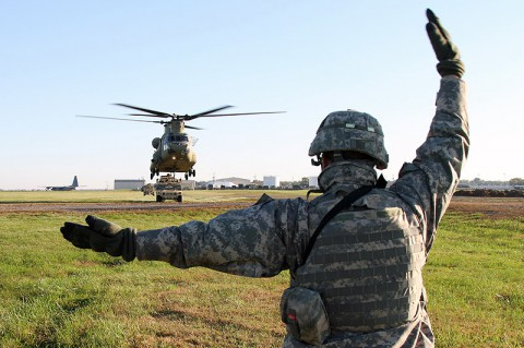 Spc. Dillon Cihak, a Sentinel crew member with Battery C, 2nd Battalion, 44th Air Defense Artillery, 101st Sustainment Brigade, 101st Airborne Division (Air Assault), uses hand and arm signals to guide a Ch-47 Chinook helicopter during a sling load operation Oct. 22 at Fort Campbell, Ky. (U.S. Army Photo by Sgt. Leejay Lockhart, 101st Sustainment Brigade Public Affairs)