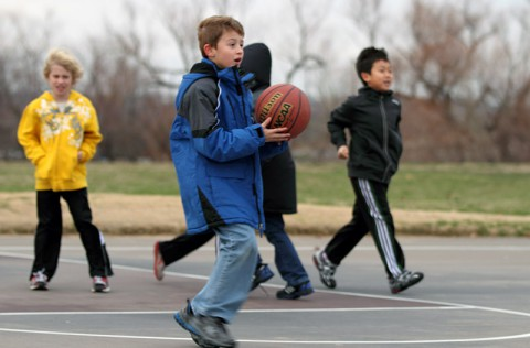 Boy holding basketball with others in background. (Copyright American Heart Association)