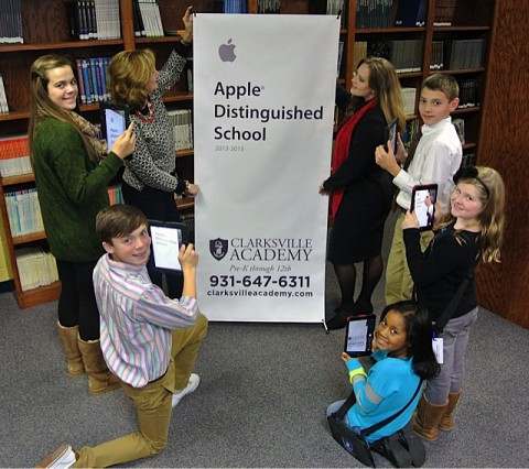 Head of School Kay Drew & Technology Director Cara Miller unveil the Apple Distinguished School banner while current students capture the moment on their school issued iPads.