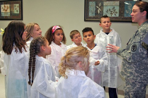 Gifted students from Barsanti Elementary School listen to Blanchfield Army Community Hospital's Laboratory Manager Maj. Anne Sterling Nov. 19, 2013 at Fort Campbell, Ky. as she explains the many ways lab staff members help medical providers diagnose and treat patients. (U.S. Army photo by Laura Boyd/RELEASED)