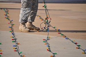 A crew member helps to untangle twinkling lights during setup for the 2012 Fort Campbell Tree Lighting Ceremony. (Heather Clark-The Fort Campbell Courier)