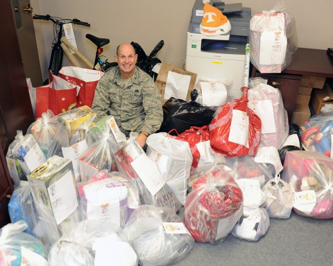 Brig. Gen. Donald Johnson, Assistant Adjutant General - Air, Tennessee National Guard, sits among the mass of items the Tennessee National Guard Joint Force Headquarters staff members collected to support the Salvation Army's annual Angel Tree Program. (Master Sgt. Robin Olsen, TN National Guard Joint Public Affairs.)