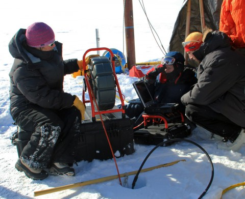 Glaciologist Lora Koenig (left) operates a video recorder that has been lowered into the bore hole to observe the ice structure of the aquifer in April 2013. (University of Utah/Clément Miège)