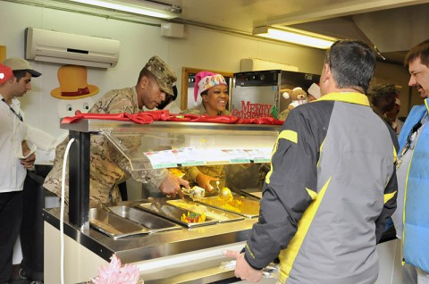 Task Force Lifeliner's Col. Charles R. Hamilton, a native of Houston, Texas, and commander of the 101st Sustainment Brigade, 101st Airborne Division (Air Assault), and Master Sgt. Katherine E. Lawson-Best, a native of New Orleans, LA, and human resources administration noncommissioned officer in charge, serve meals during Christmas lunch, Dec. 25, 2013 at the Koele Dining Facility at Bagram Air Field, Parwan province, Afghanistan. As tradition has it, senior military leaders served their troops a feast worthy of the Holiday. (U.S. Army photo by Sgt. Sinthia Rosario, Task Force Lifeliner Public Affairs)