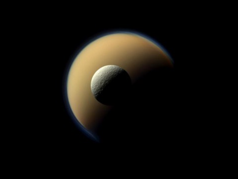 Saturn's largest and second largest moons, Titan and Rhea, appear to be stacked on top of each other in this true-color scene from NASA's Cassini spacecraft. (NASA/JPL-Caltech/Space Science Institute)