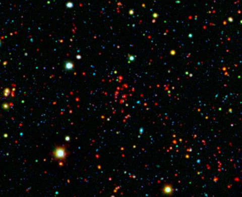 The collection of red dots seen near the center of this image show one of several very distant galaxy clusters discovered by combining ground-based optical data from the National Optical Astronomy Observatory's Kitt Peak National Observatory with infrared data from NASA's Spitzer Space Telescope. This galaxy cluster, named ISCS J1434.7+3519, is located about 9 billion light-years from Earth. (NASA/JPL-Caltech/KPNO/University of Missouri-Kansas City)