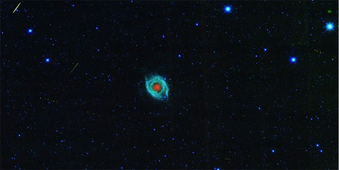 A dying star, called the Helix nebula, is shown surrounded by the tracks of asteroids in an image captured by NASA's Wide-field Infrared Survey Explorer, or WISE. (NASA/JPL-Caltech/UCLA)