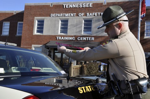 Tennessee State Trooper ties Mothers Against Drunk Driving ribbon on his patrol car.