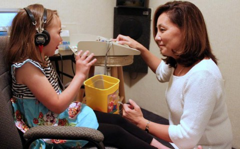 Dr. Emi Lejeune conducts a hearing evaluation on a young patient (Bill Larson Clarksville Online)