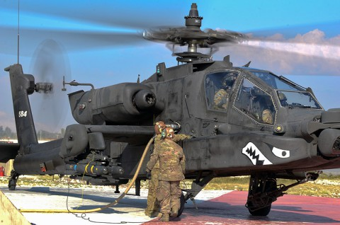 Task Force Attack Soldiers with the 159th Combat Aviation Brigade conduct a hot refuel on an AH-64D Apache helicopter. ( Spc. Joseph Green)