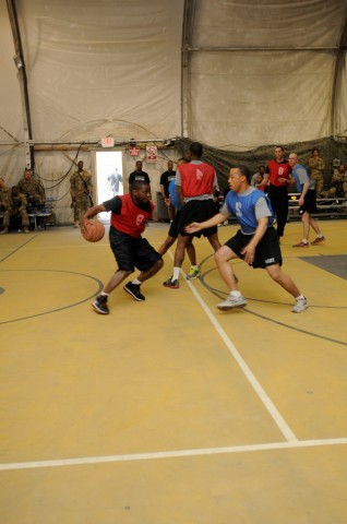 Sgt. Christopher A. Edwards, a native of Virginia Beach, VA, and help desk administrator with Task Force Lifeliner, dribbles a basketball during a game between officers and enlisted soldiers, Jan. 5, 2014, at Bagram Air Field, Parwan province, Afghanistan. During the game the officers wore blue jerseys and the enlisted wore red jerseys. (Sgt. Sinthia Rosario, Task Force Lifeliners Public Affairs)