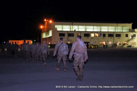 The returning soldiers approach the hanger and their waiting families