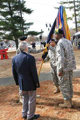 "Col. J.B. Vowell, the commander of 3rd Brigade Combat Team ""Rakkasans,"" 101st Airborne Division (Air Assault), passes the unit colors to the incoming senior enlisted advisor Command Sgt. Maj. Walter Tagalicud during the Rakkasan Activation Ceremony here Feb. 19, 2014. (Photo by Sgt. Brian Smith-Dutton, 3rd BCT Public Affairs)"
