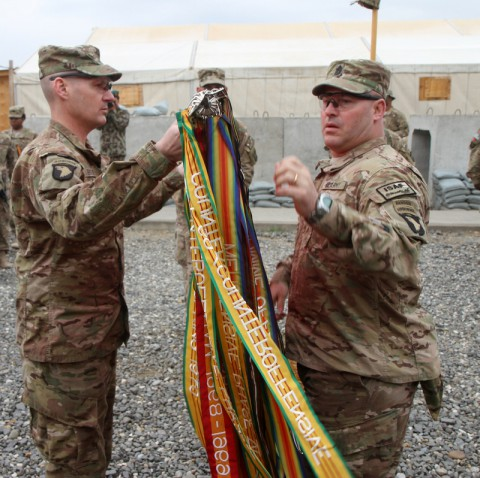 U.S. Army Col. Peter Benchoff, commander of Task Force Strike, and Command Sgt. Maj. Brendan Haywood, Task Force Strike's sergeant major, unfurl the unit colors during a transfer of authority ceremony March 3, 2014 at Forward Operating Base Gamberi. (Sgt. David Cox/U.S. Army)