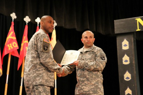 Sgt. Michael Nunes, a gunner with Battery B, 2nd Battalion, 320th Field Artillery Regiment, 1st Brigade Combat Team, 101st Airborne Division, receives his Charge of the Noncommissioned Officer from Command Sgt. Maj. Brian Veney, the command sergeant major of 426th Brigade Support Battalion, during 2nd Bn., 320th FAR's NCO Induction Ceremony March 20 at the Morale, Welfare and Readiness' Dale Waryrnen Recreation Center. (Sgt. Jon Heinrich/U.S. Army)