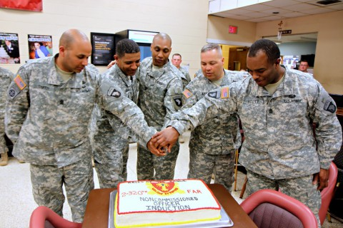 The command sergeants major and first sergeants cut the cake after conducting a noncommissioned officer induction ceremony for 16 soldiers from 2nd Battalion, 320th Field Artillery Regiment, 1st Brigade Combat Team, 101st Airborne Division, March 20 at the Morale, Welfare and Readiness' Dale Waryrnen Recreation Center. (Sgt. Jon Heinrich/U.S. Army)