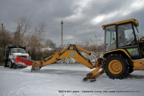 The stuck snow plow and the backhoe loader