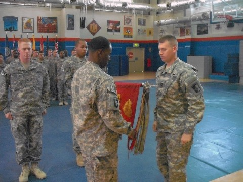 Capt. Jerad N. Hoffmann and 1st Sgt. David L. Mahatha uncase the 594th Transportation Company guidon at the Relief in Place/Transfer of Authority (RIPTOA) ceremony March 28, at Camp Arifjan, Kuwait. (U.S. Army photo by 1st Lt. Alexander W. Muth, 594th Transportation Company, 129th Combat Sustainment Support Battalion)