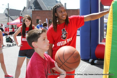 APSU students watch as a young boy demonstrates his basketball skills at the Rivers and Spires Festival Sports Zone