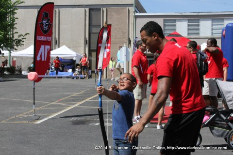 APSU students help a young boy with his archery skills at the 2014 Rivers and Spires Festival Sports Zone