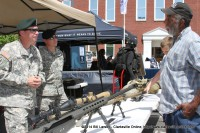5th Special Forces Group Soldiers talk with a military veteran about the weapons they use on the modern battlefield