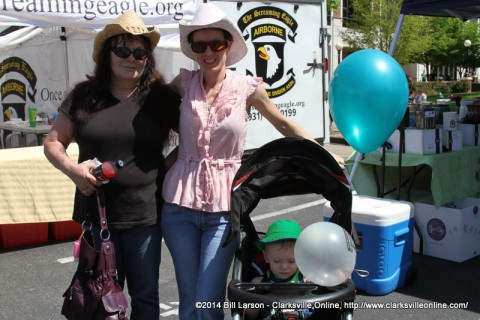 A family poses for a photograph in front of the 101st Airborne Association booth at the 2014 Rivers and Spires Festival