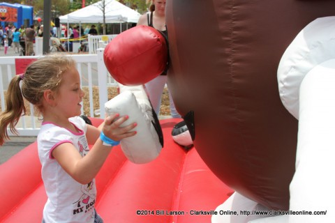 A young girl places lips on a giant Mr. Potato Head Inflatable.