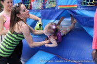 A mom pulls her young daughter out of one of the inflatables
