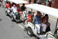 Festival Director Jessica Goldberg (right front) rides with the former Festival Director Doug Barber and other dignitaries in the Children's Parade at the 2014 Rivers and Spires Festival in Historic Downtown Clarksville