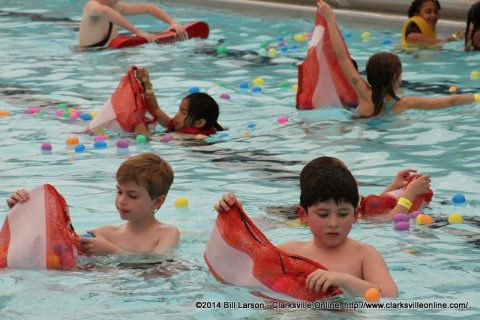 Children gather eggs from the Pool at the Indoor Aquatic Center during the Wettest Egg Hunt on Saturday